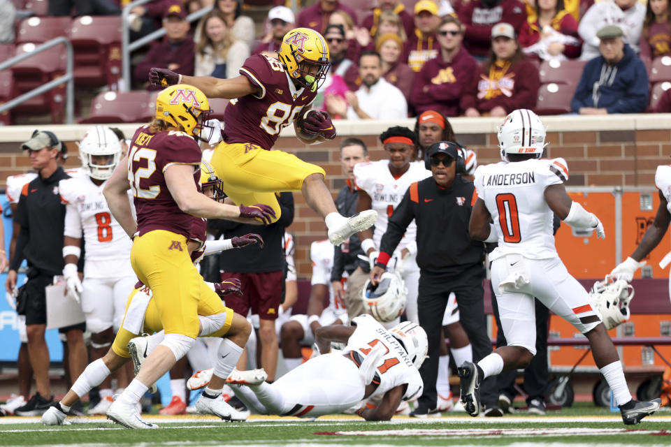 Minnesota tight end Brevyn Spann-Ford (88) leaps over Bowling Green cornerback Marcus Sheppard (21) during an NCAA college football game Saturday, Sept. 25, 2021, in Minneapolis. (AP Photo/Stacy Bengs)