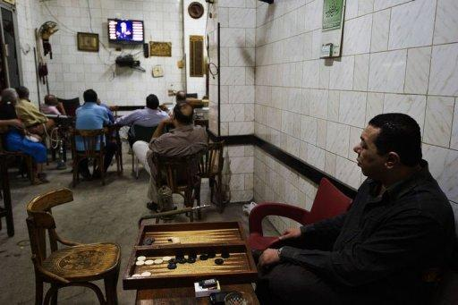 Egyptians watch a live television debate at a coffee shop in Cairo