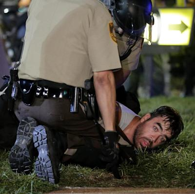 A man is detained by police during a protest Monday, Aug. 18, 2014, for Michael Brown, who was killed by a police officer Aug. 9 in Ferguson, Mo. Brown's shooting has sparked more than a week of protests, riots and looting in the St. Louis suburb. (AP Photo/Charlie Riedel)