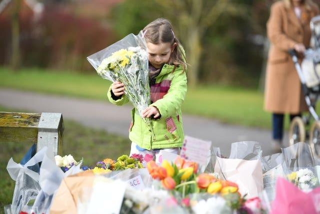 Noelle Simmons, four, leaves a floral tribute outside the home of Captain Sir Tom Moore in Marston Moretaine, Bedfordshire