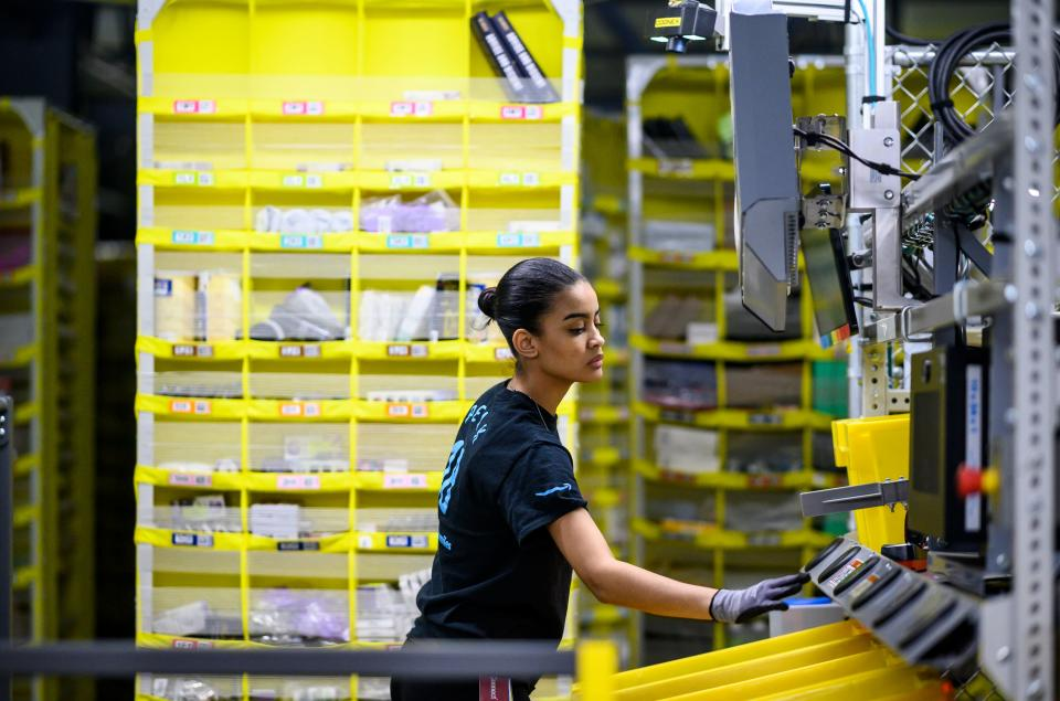 A woman works at a distrubiton station at the 855,000-square-foot Amazon fulfillment center in Staten Island, one of the five boroughs of New York City, on February 5, 2019. - Inside a huge warehouse on Staten Island thousands of robots are busy distributing thousands of items sold by the giant of online sales, Amazon. (Photo by Johannes EISELE / AFP) (Photo credit should read JOHANNES EISELE/AFP via Getty Images)