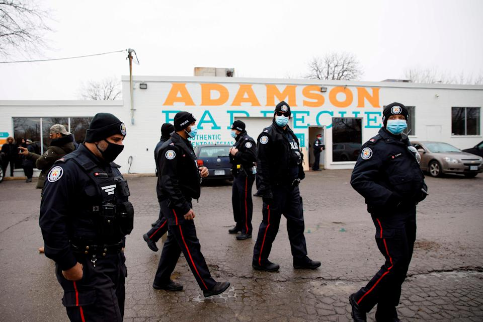 <p>Police gather in the car park of Adamson Barbecue</p> (AFP via Getty Images)