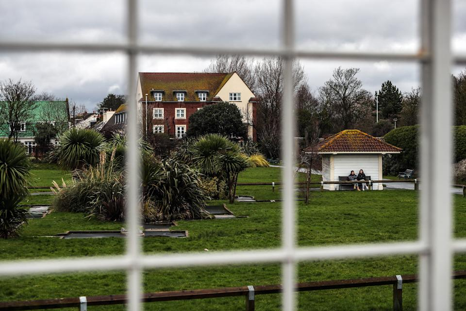 General view of two girls sitting on a park bench in Worthing, as the UK continues in lockdown due to the coronavirus pandemic.