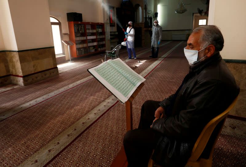 FILE PHOTO: Palestinian reads Koran as a worker disinfects a mosque as a preventive measure against the coronavirus, in Ramallah in the in the Israeli-occupied West Bank