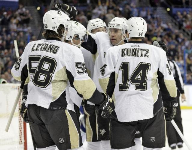 Pittsburgh Penguins left winger Chris Kunitz (14) celebrates his goal against the Tampa Bay Lightning with teammates, including Kris Letang (58) and Pascal Dupuis (9) during the first period of an NHL hockey game on Friday, Nov. 29, 2013, in Tampa, Fla. (AP Photo/Chris O'Meara)