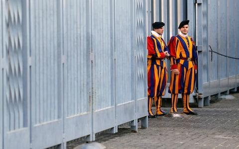 Vatican Swiss Guards in their distinctive multi-coloured uniform stand at the Sant'Uffizio entrance to the Vatican - Credit: Andrew Medichini/AP