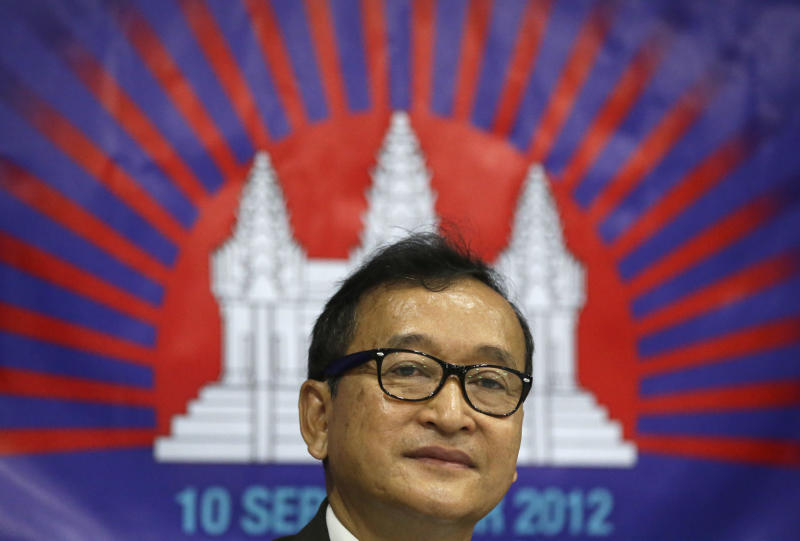 FILE - In this Sept. 10, 2012 file photo, Cambodian opposition leader Sam Rainsy who is currently living in exile in France, talks about the opposition's plans for next year's elections in Cambodia during the launching of the International Parliamentary Committee for Democratic Elections in Cambodia with Philippine Sen. Franklin Drilon, in San Juan, east of Manila, Philippines. Cambodian Prime Minister Hun Sen engineered a pardon for his most prominent rival Rainsy Friday, clearing the way for the self-exiled politician to return home and campaign in this month's general election. Rainsy has lived abroad since 2009 to avoid an 11-year prison term on charges widely seen as politically motivated. (AP Photo/Bullit Marquez, File)