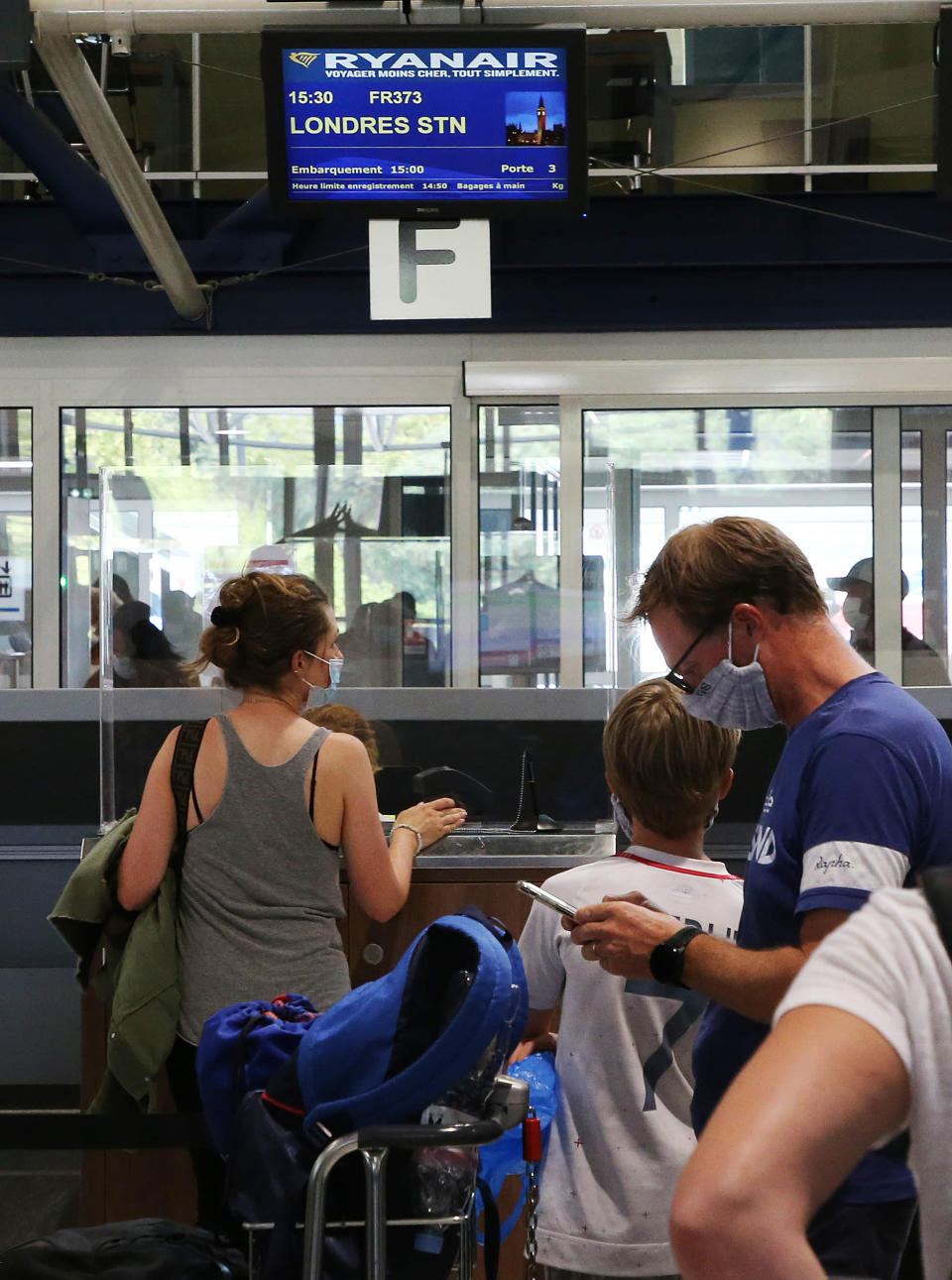 People check-in for a flight to London at the Biarritz airport, southwestern France, Friday Aug.14, 2020. British holidaymakers in France were mulling whether to return home early Friday to avoid having to self-isolate for 14 days following the U.K. government's decision to reimpose quarantine restrictions on France amid a recent pick-up in coronavirus infections. (AP Photo/Bob Edme)