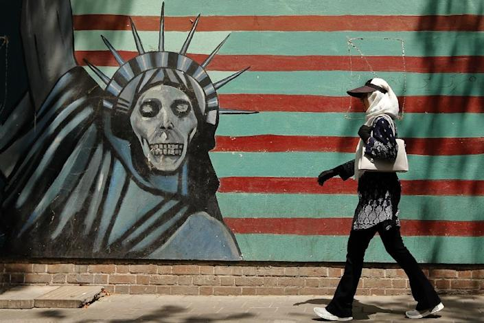 An Iranian woman walks past a mural depicting the Statue of Liberty, painted on the wall of the former US embassy in the capital Tehran on August 7, 2018 (AFP Photo/ATTA KENARE)