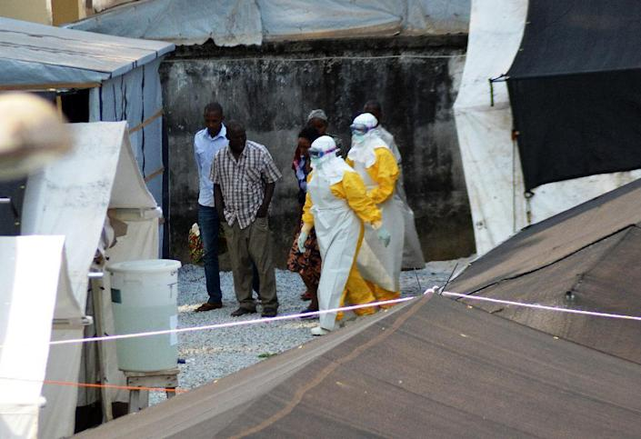 Health workers wearing protective suits walk in an isolation center for people infected with Ebola at Donka Hospital in Conakry on April 14, 2014 (AFP Photo/Cellou Binani)
