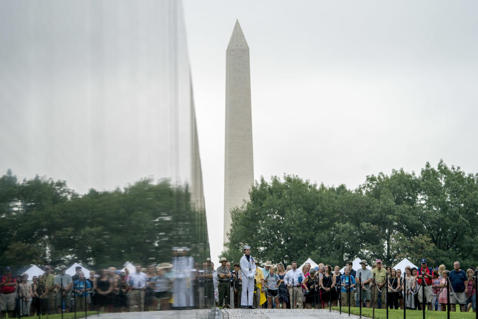 A crowd gathers before Cindy McCain, wife of, Sen. John McCain, R-Ariz., arrives to lay a wreath at the Vietnam Veterans Memorial in Washington, Saturday, Sept. 1, 2018, during a funeral procession to carry the casket of her husband from the U.S. Capitol to National Cathedral for a memorial service. McCain served as a Navy pilot during the Vietnam War and was a prisoner of war for more than five years. (AP Photo/Andrew Harnik, Pool)
