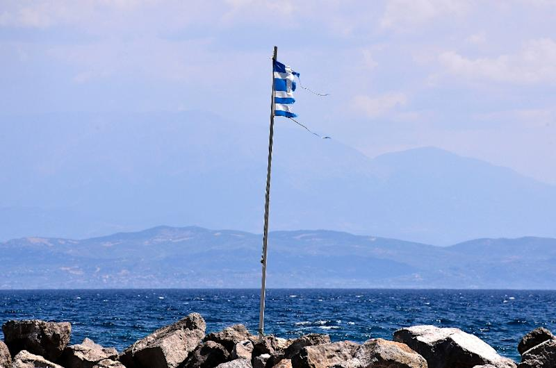 A torn Greek flag is seen fluttering near Antirio, south-west of Athens, on August 9, 2015 (AFP Photo/Louisa Gouliamaki)