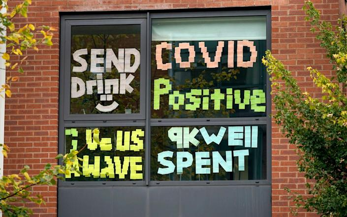 Signs made by students are displayed in a window of their locked down accommodation buildingin Manchester, England - Christopher Furlong/Getty Images