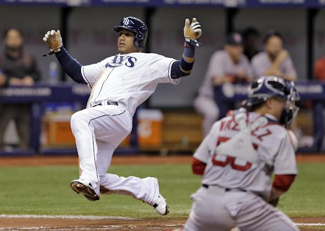 Tampa Bay Rays' Yunel Escobar, left, scores in front of Boston Red Sox catcher Christian Vazquez on an RBI-single hit by Kevin Kiermaier off Red Sox pitcher John Lackey during the fourth inning of a baseball game on Saturday, July 26, 2014, in St. Petersburg, Fla. (AP Photo/Chris O'Meara)