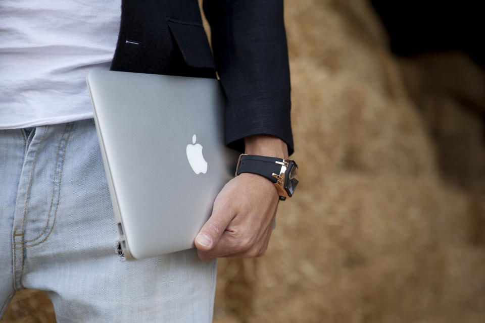A man carrying an Apple MacBook. (PHOTO: Getty Images)