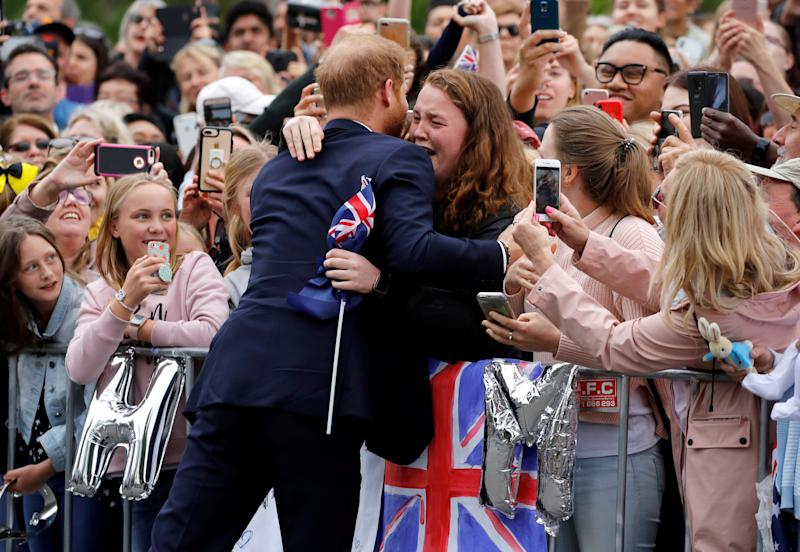 Britain's Prince Harry hugs Melbourne university student India Brown during his tour of Melbourne with Duchess of Sussex, Meghan Markle.