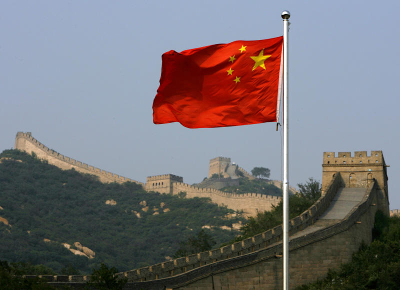 A Chinese flag flies in front of the Great Wall of China. Source: Reuters