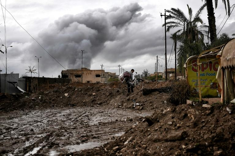 An Iraqi carries a bicycle in West Mosul during the offensive to retake the city from Islamic State group, on March 16, 2017