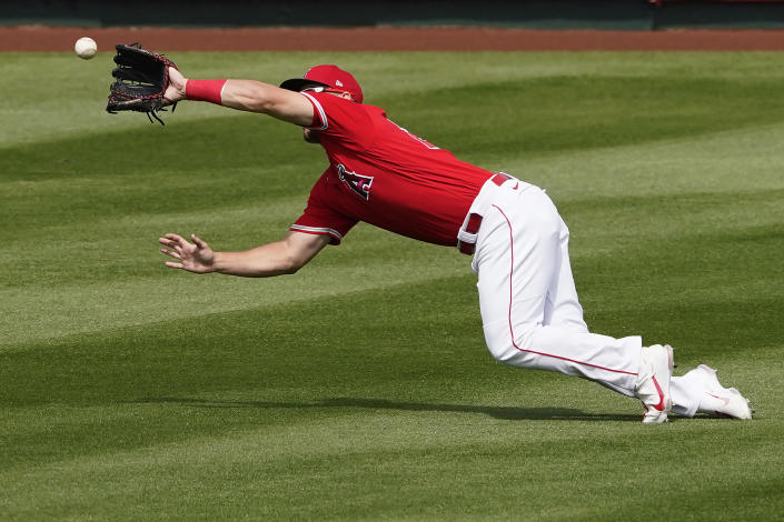 Los Angeles Angels' Mike Trout catches a fly out by Cincinnati Reds' Kyle Holder during the inning of a spring training baseball game, Monday, March 15, 2021, in Tempe, Ariz. (AP Photo/Matt York)