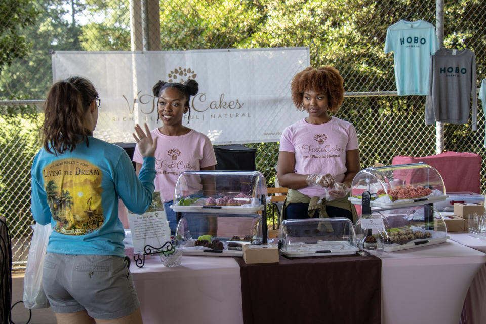 Jasmyn Reddicks, left, owner of VTasteCakes, talks with a customer at the Athens, Ga., Farmer's Market. The new bakery focuses on vegan cupcakes with plans for a line of cakes in development.