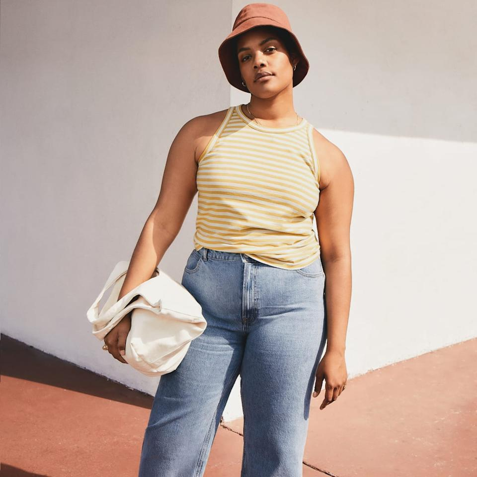 Model wears The Organic Cotton Cutaway Tank in yellow stripe with blue jeans. Image via Everlane.