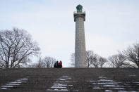 A couple sits on the steps of Fort Greene Park's Monument Plaza at dusk in the Brooklyn borough of New York, Dec. 23, 2020. The monument marks the site of a crypt for more than 11,500 prison ship martyrs who were buried in a tomb near the Brooklyn Navy Yard. (AP Photo/Kathy Willens)