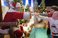 Julianna, 3, and Dylan, 5, Lasczak visit with Santa through a transparent barrier at a Bass Pro Shop in Bridgeport, Conn., Tuesday, Nov. 10, 2020. Santa Claus is coming to the mall — just don't try to sit on his lap. Malls are doing all they can to keep the jolly old man safe from the coronavirus, including banning kids from sitting on his knee, no matter if they've been naughty or nice. (AP Photo/Seth Wenig)