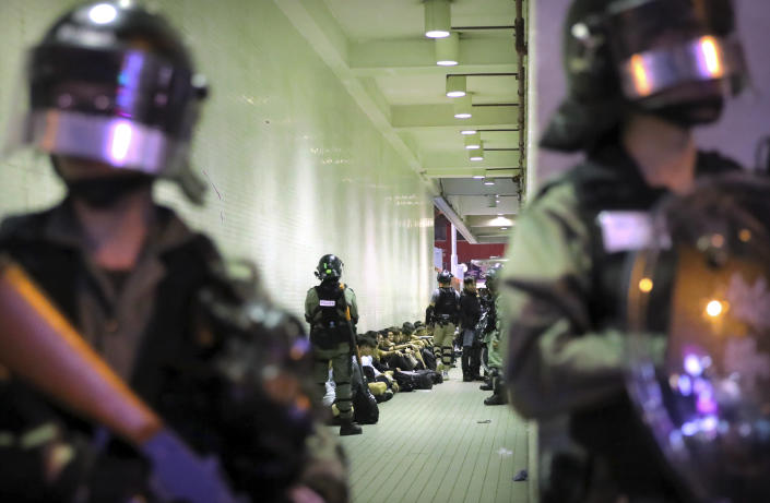 In this Saturday, Nov. 2, 2019, file photo, police in riot gear stand over people detained during a protest in Hong Kong. Hong Kong riot police fired multiple rounds of tear gas and used a water cannon Saturday to break up a rally by thousands of masked protesters demanding meaningful autonomy after Beijing indicated it could tighten its grip on the Chinese territory. (AP Photo/Kin Cheung, File)