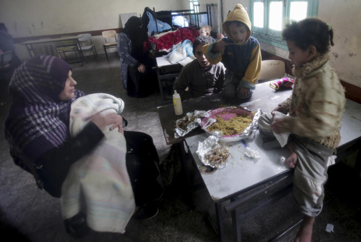Palestinian family members eat their lunch at a school after evacuated from their flooded home following heavy rains in Gaza City, Saturday, Dec. 14, 2013. Hundreds of houses were flooded following a rain storm in Gaza. Early snow has surprised many Israelis and Palestinians as a blustery storm, dubbed Alexa, brought gusty winds, torrential rains and heavy snowfall to parts of the Middle East. (AP Photo/Adel Hana)