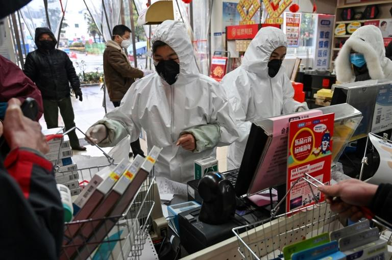 People in Wuhan are buying medical supplies in pharmacies where staff wear full body-suits, gloves and masks