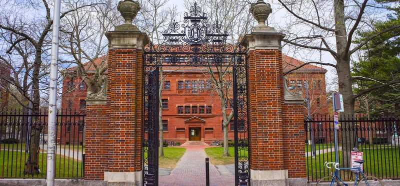 Brick pillar and wrought iron fence entrance to Harvard.