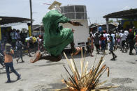 """A person jumps over a bonfire on the street as members of the gang led by Jimmy Cherizier, alias Barbecue, a former police officer who heads a gang coalition known as """"G9 Family and Allies,"""" march to demand justice for slain Haitian President Jovenel Moise in La Saline neighborhood of Port-au-Prince, Haiti, Monday, July 26, 2021. Moise was assassinated on July 7 at his home. (AP Photo/Matias Delacroix)"""