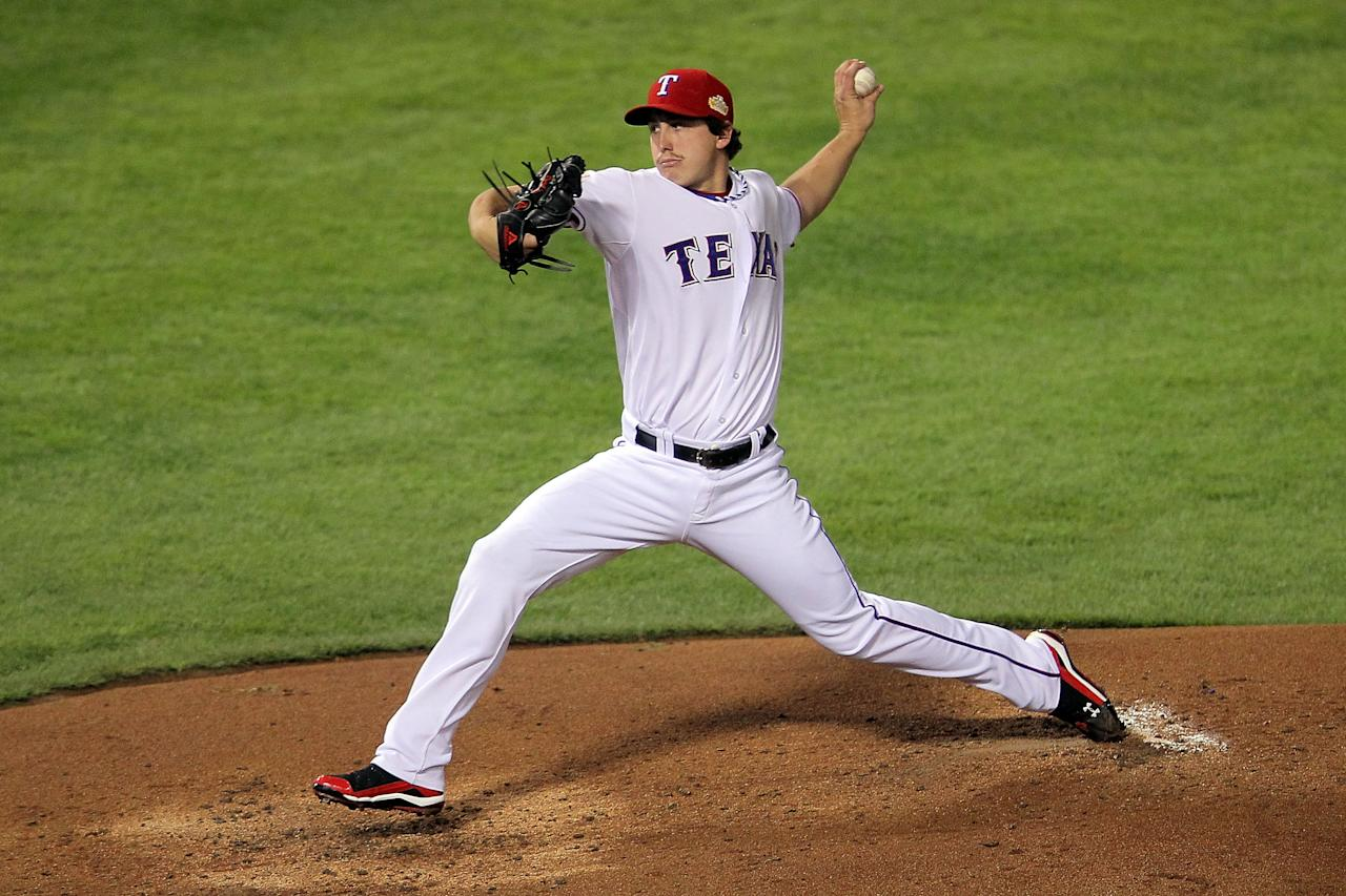 ARLINGTON, TX - OCTOBER 23:  Derek Holland #45 of the Texas Rangers pitches in the second inning during Game Four of the MLB World Series against the St. Louis Cardinals at Rangers Ballpark in Arlington on October 23, 2011 in Arlington, Texas.  (Photo by Doug Pensinger/Getty Images)