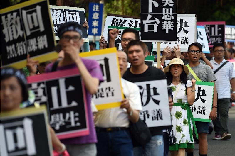 "Activists march with placards that read, ""Fix the disputed curriculum"" during a demonstration by Taiwanese students and activists against the island's China-centric curriculum changes, in Taipei on August 2, 2015 (AFP Photo/Sam Yeh)"