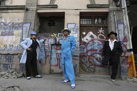 Guardarrama Tapia, Jesus Gonzalez de la Rosa and Flores Mujica wears their Pachuco outfits while posing for a photograph next to a wall with graffiti in Mexico City