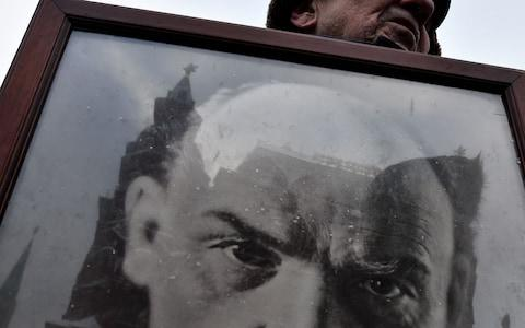 A Communist Party supporter carries a portrait of Lenin during a memorial ceremony on Red Square in 2016. - Credit: Kirril Kudryavtsev/AFP/Getty Images