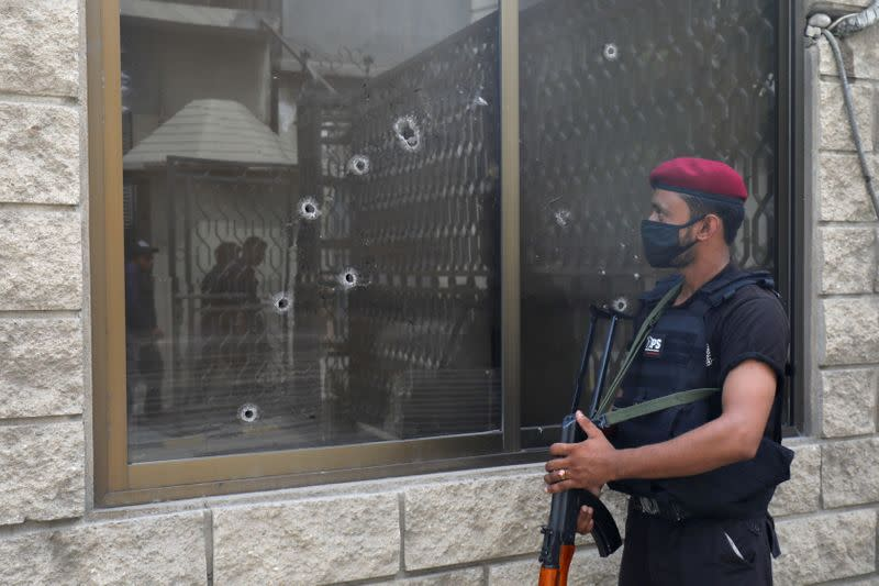 Police officer stands guard next to a bullet riddled window at the Pakistan Stock Exchange building after an attack in Karachi