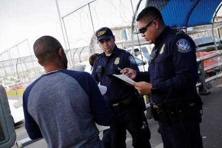 U.S. Customs and Border Protection officers inspect documents from a Honduran migrant seeking asylum at Paso del Norte International border bridge, in this picture taken from Ciudad Juarez
