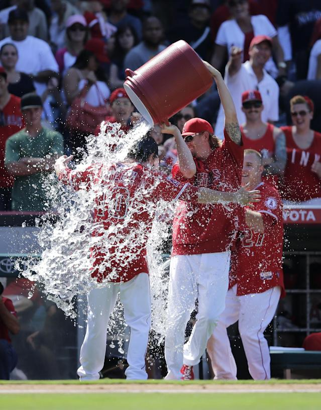 Los Angeles Angels starting pitcher Jered Weaver, center, dumps water over Grant Green, left, as they celebrate Green's ninth-inning walk-off single against the Seattle Mariners after a baseball game on Sunday, July 20, 2014, in Anaheim, Calif. The Angels won 6-5. (AP Photo/Jae C. Hong)