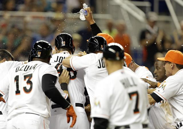 Miami Marlins players surround Giancarlo Stanton at the plate after he hit a grand slam to defeat the Seattle Mariners 8-4 during the ninth inning of an interleague baseball game on Friday, April 18, 2014, in Miami. (AP Photo/Lynne Sladky)