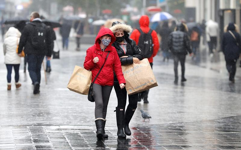 Women wearing face masks carry shopping bags in Liverpool as the city awaits news on potential further lockdown restrictions - REUTERS/Phil Noble