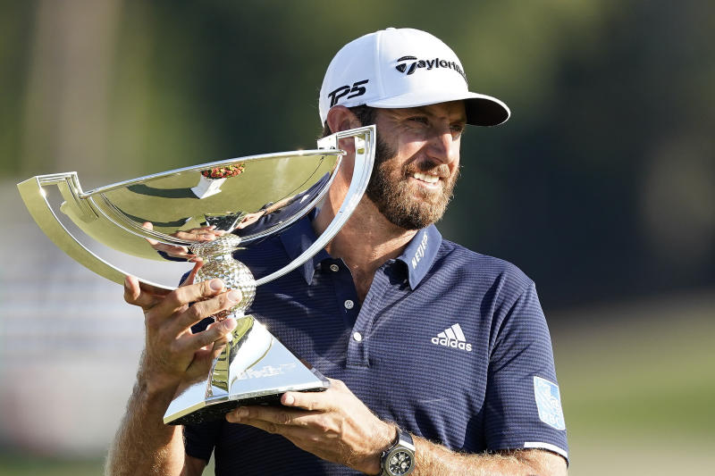 Dustin Johnson holds up the FedEx Cup trophy after winning the Tour Championship golf tournament on Monday, Sept. 7, 2020 at Lake Golf Club in Atlanta. (AP Photo/John Bazemore)