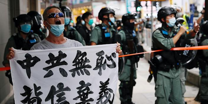 "An anti-national security law protester holds a banner reading ""Chinese communist party is shameless, break the promises"" during a march at the anniversary of Hong Kong's handover to China from Britain in Hong Kong, China July 1, 2020."