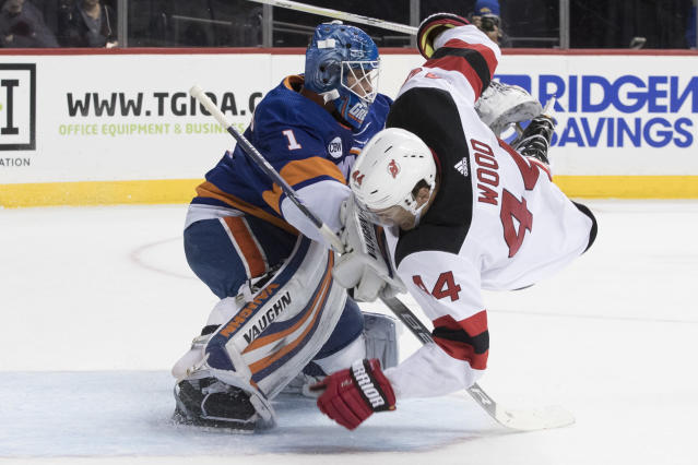 New Jersey Devils left wing Miles Wood (44) flips over New York Islanders goaltender Thomas Greiss (1) during the first period of an NHL hockey game, Saturday, Nov. 3, 2018, in New York. (AP Photo/Mary Altaffer)