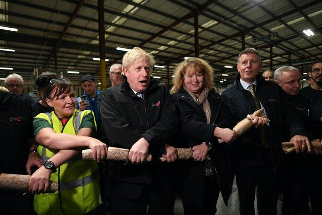 Prime Minister Boris Johnson pulls Christmas crackers with staff during a visit to IG Design Group in Hengoed (Stefan Rousseau/PA)
