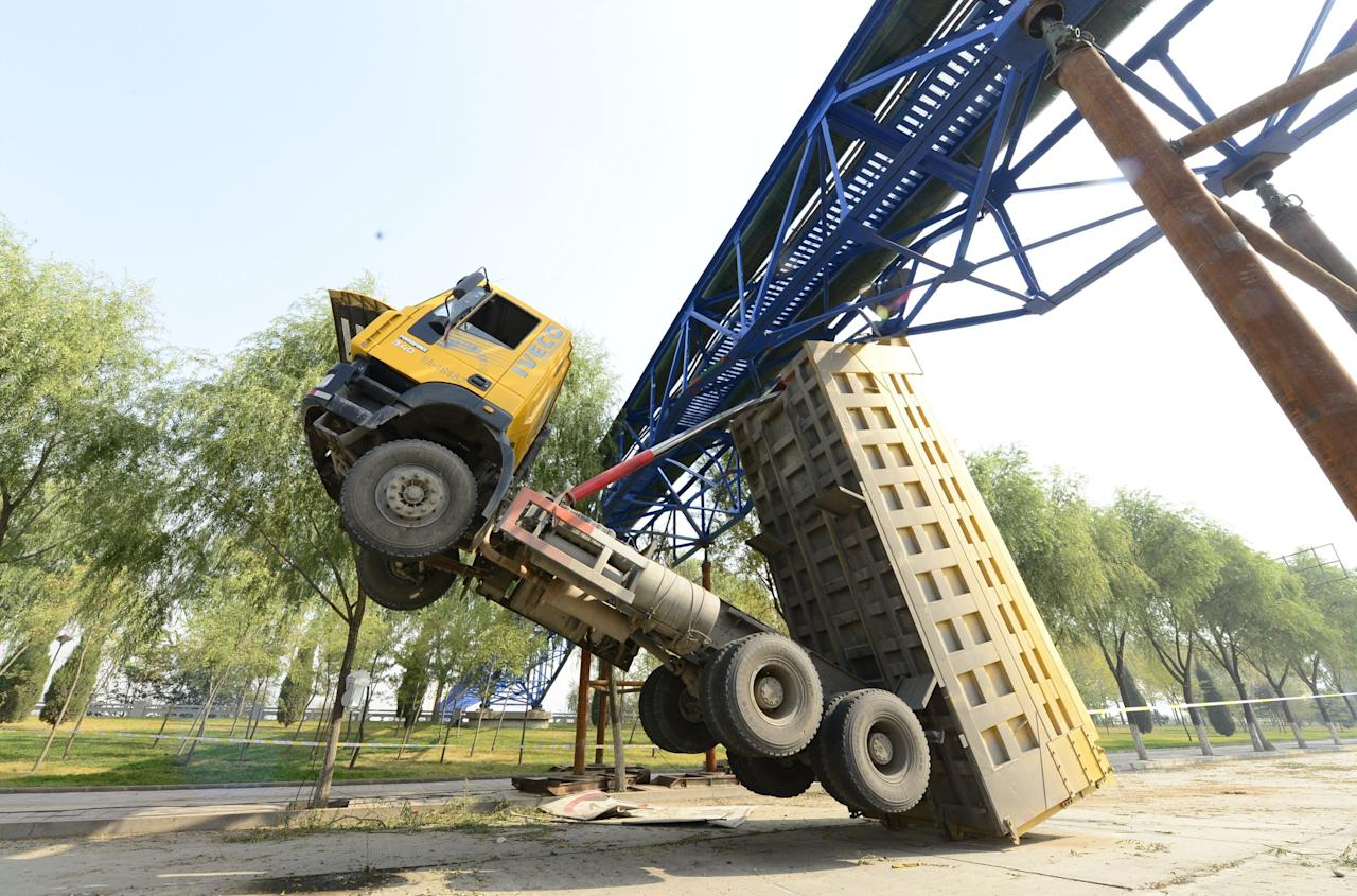 This dump truck became wedged under a bridge for five days in Lanzhou, in China's Gansu Province, after its driver claimed the loader 'suddenly flipped up' as he approached. (Rex)