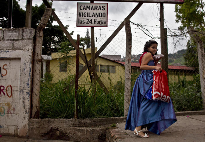 """In this May 31, 2013 photo, a girl who attended her school's beauty contest walks home in a princess outfit under a sign that reads in Spanish; """"surveillance cameras 24 hours"""" near downtown Tegucigala, Honduras. In the midst of a scandal over the police shooting of a university president's son, the government of Honduras launched an unprecedented effort last year to clean up a U.S.-backed police force widely seen as deeply brutal and corrupt. By April of this year, the Honduran government said it had dismissed a mere seven members of the 13,800-person force, a vivid illustration of the lack of progress in a year-old effort aided by the U.S. to reform police in a country that's swamped with U.S.-bound cocaine and wracked by one of the world's highest homicide rates. (AP Photo/Esteban Felix)"""
