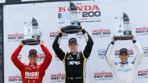 Podium finishers Marcus Ericsson, second place, Josef Newgarden, race winner and Alex Palou, third place, raise their trophies in Victory Lane during an IndyCar race at Mid-Ohio Sports Car Course in Lexington, Ohio, Sunday, July 4, 2021. (AP Photo/Tom E. Puskar)