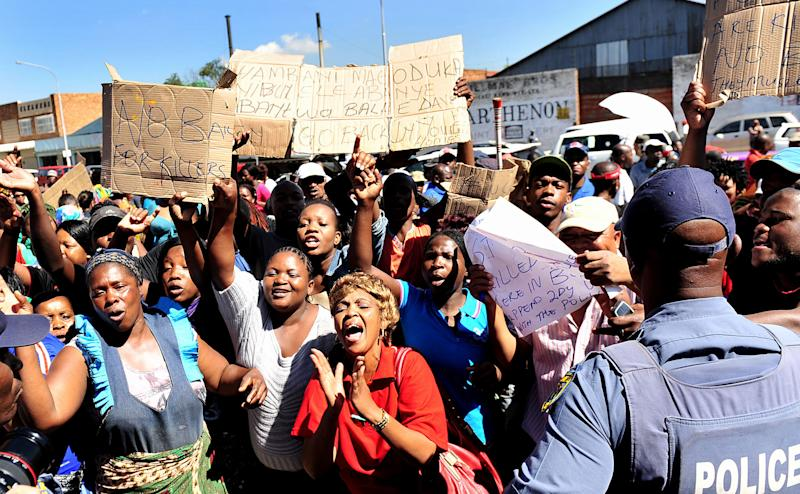 Demonstrators protest outside the  court in Benoni ,South Africa,  Monday March 4, 2013, ahead of the bail application for the eight South African police officers facing murder charges in last week's death of a Mozambican taxi driver dragged by a police vehicle along the street. The case has been postponed until Friday. Protesters were demanding no bail be granted to the officers, insisting the horrific videotaped scenes of last Tuesday's abuse should be enough to keep all behind bars. (AP Photo)