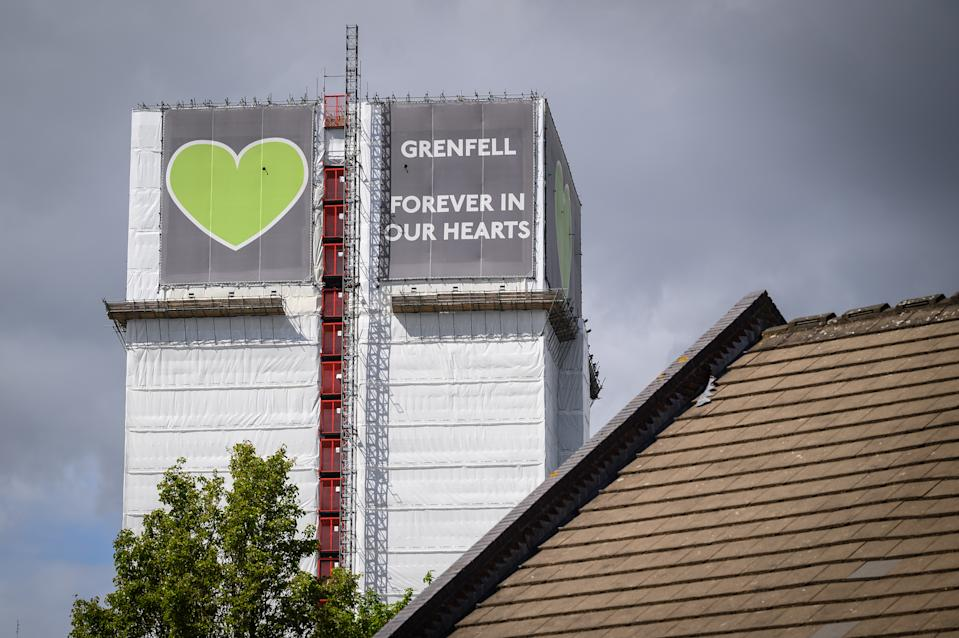 LONDON, ENGLAND - MAY 12: The covered structure of Grenfell Tower is seen above a nearby housing estate on May 12, 2021 in London, England. The Ministry of Housing Communities and Local Government (MHCLG) has announced that it is considering demolishing the building, but that it will be at least a year before any decision on the future of the tower is implemented. 72 people lost their lives in a blaze at the tower block in west London in June 2017. (Photo by Leon Neal/Getty Images)